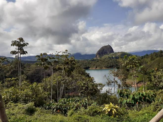 A large rock sits in the distance across a jungle landscape and a glimpse of a river in the foreground. The sky is mostly cloudy.