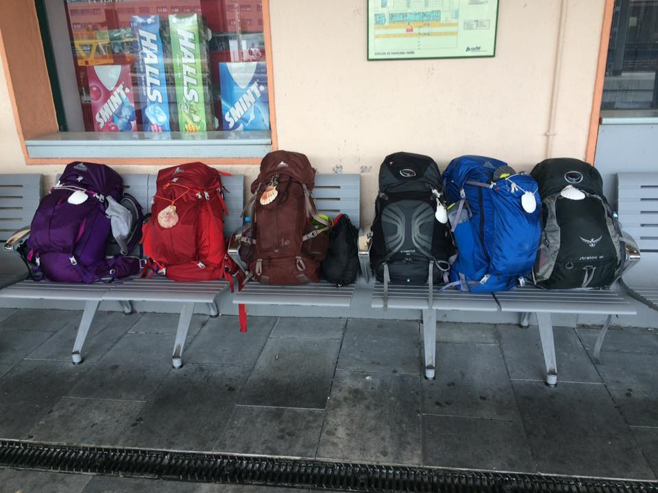 6 backpacking backpacks on a bench at a train station in France. Each backpack has a shell on the front signifying the Camino de Santiago.